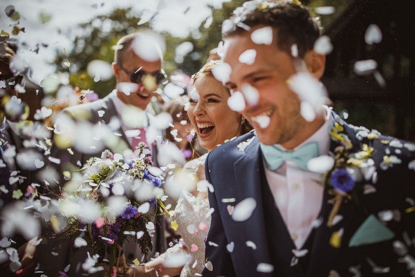 Bride and groom walking through shower of confetti - Picture by Neil Jackson Photographic