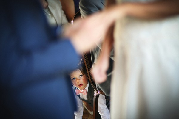 Pageboy looking out from under chair during wedding ceremony - Picture by Neale James