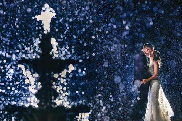 Bride and groom kissing behind spray of water fountain - Picture by Ash Davenport of Miki Photography