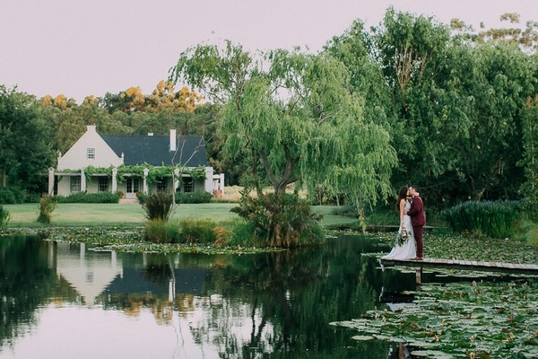 Bride and groom kissing by lake at Natte Valleij wedding