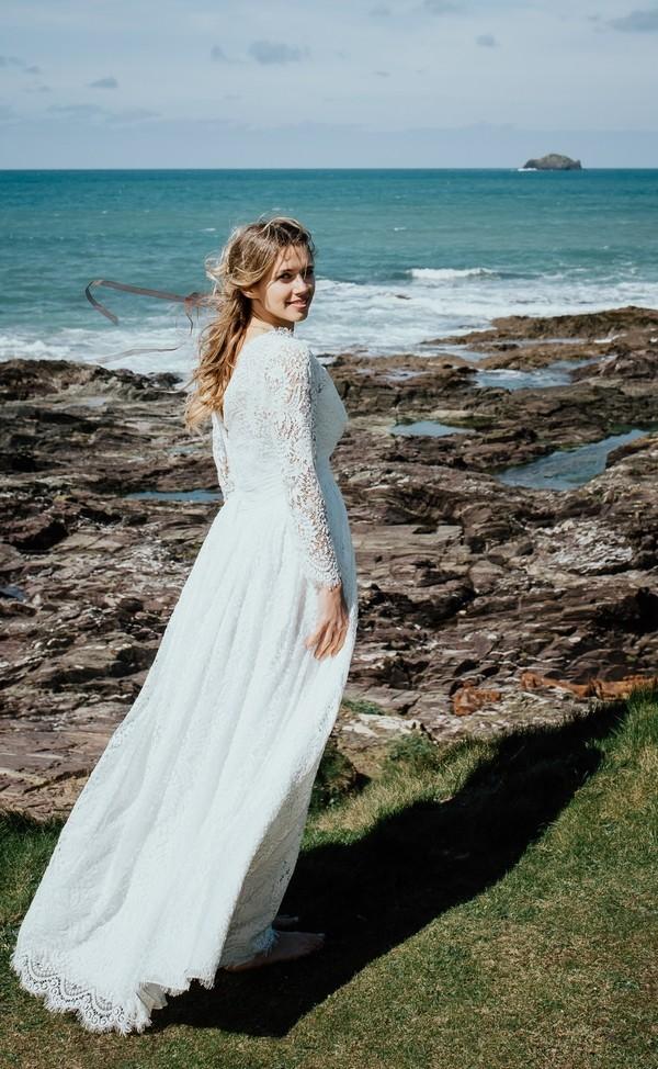 Bride by rocks on beach