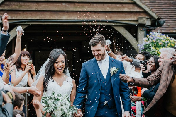 Bride and groom walking through confetti shower