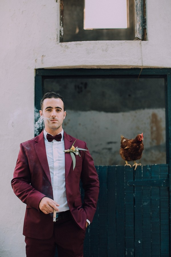 Groom smoking cigar with chicken behind him