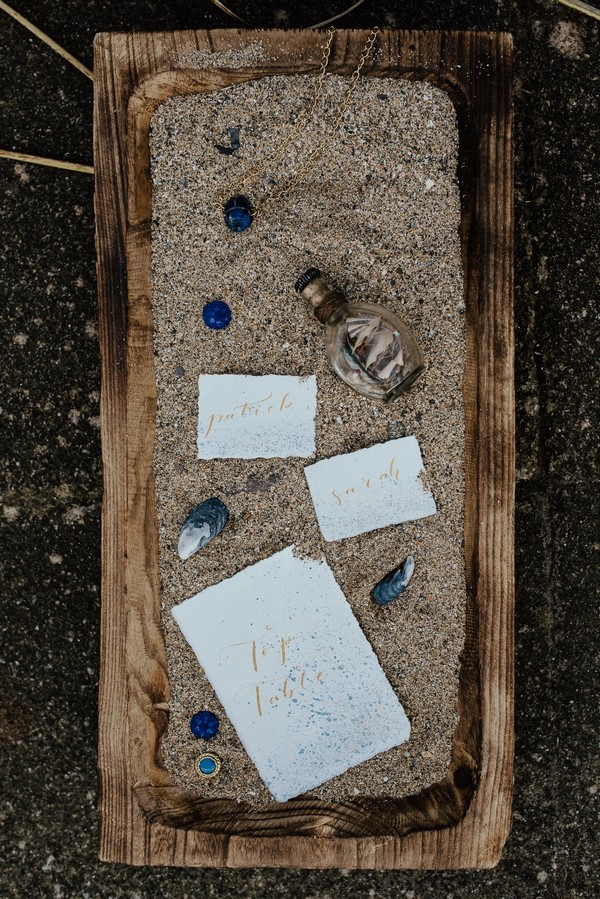 Wedding stationery with shells in sand