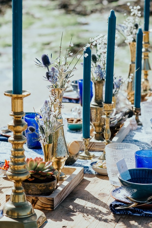 Gold candlesticks with blue candles down middle of wedding table