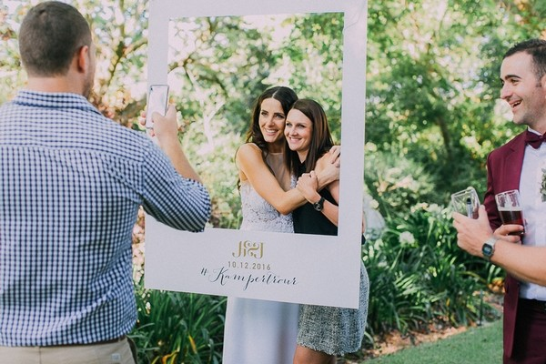 Bride and friend having picture taken behind personalised wedding frame