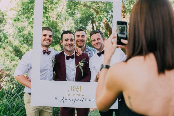 Groomsmen having picture taken behind personalised wedding frame