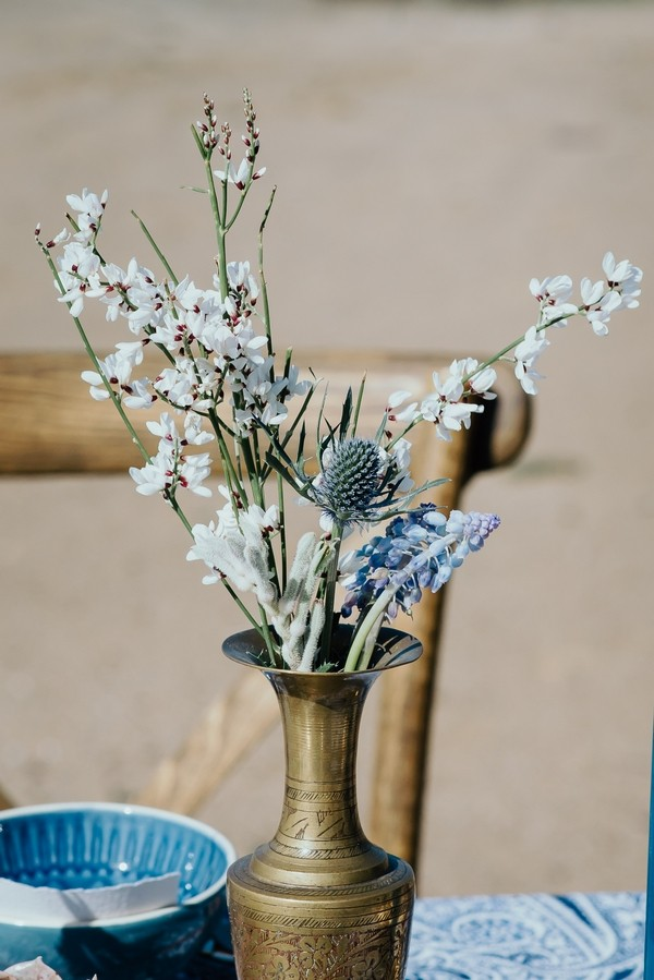 White flowers and thistle in gold vase
