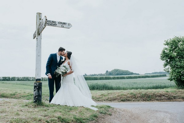Bride and groom kissing by sign post