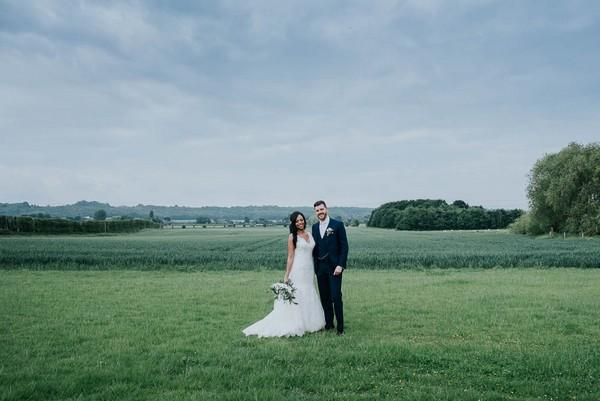 Bride and groom standing in field