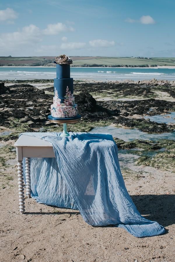 Blue wedding cake on table on beach