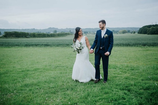 Bride and groom holding hands as they walk across field