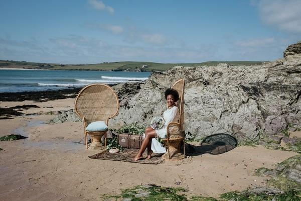 Bride sitting on chair by rocks on beach