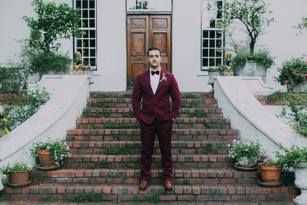 Groom in burgundy suit on steps of Natte Valleij