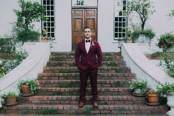 Groom in burgundy suit on steps of Natte Valleij
