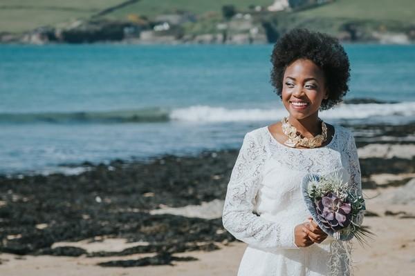 Bride holding bouquet as she walks on beach