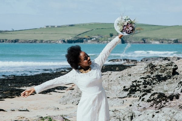 Bride holding out arms on beach