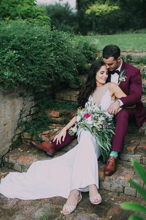 Bride sitting between groom's legs on steps