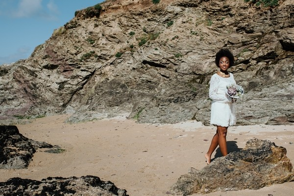 Bride walking by rocks on beach