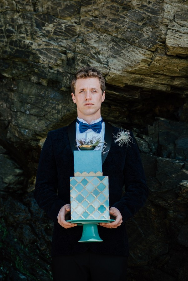 Groom holding light blue wedding cake