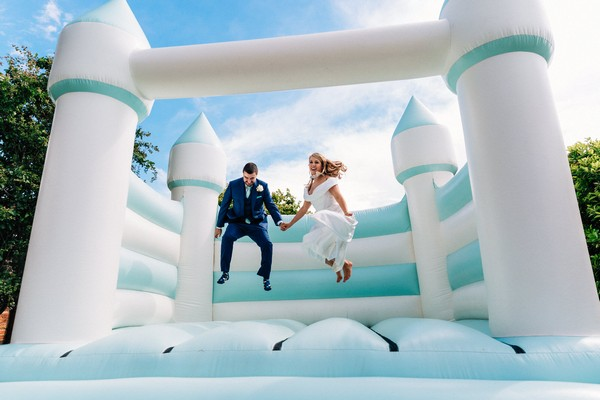 Bride and groom on bouncy castle - Picture by Damion Mower Photography
