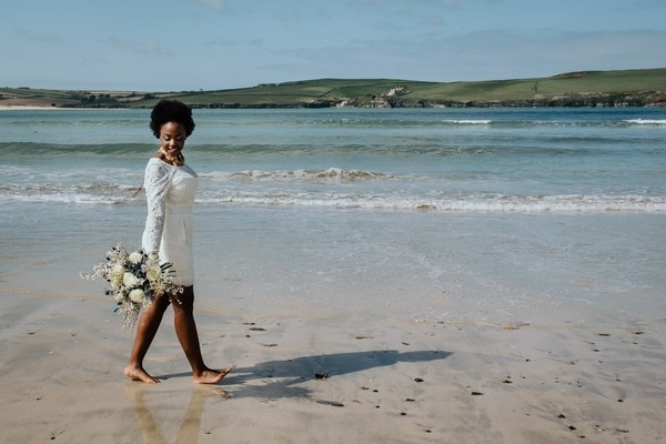 Bride walking across beach
