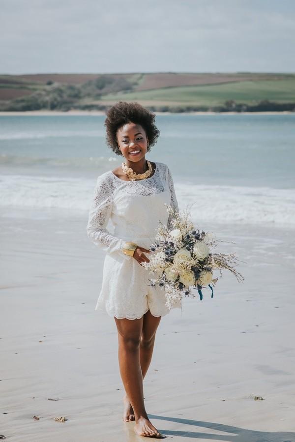 Bride standing on beach holding bouquet