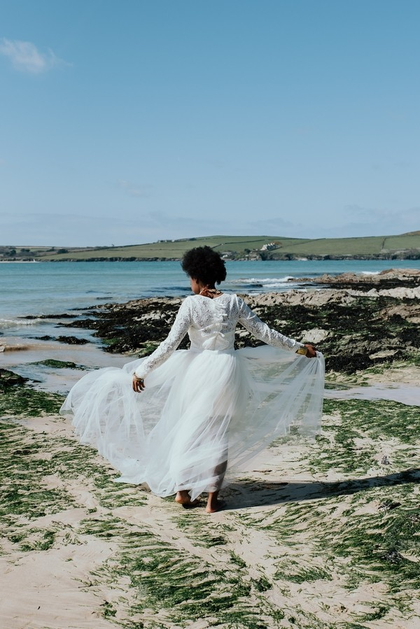 Bride holding out skirt as she walks on beach