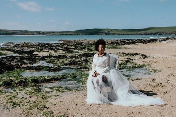 Bride sitting on chair on beach