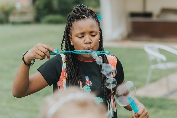 Girl blowing bubbles with bubble wand