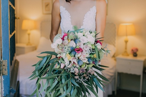Bride holding large bouquet of flowers and foliage