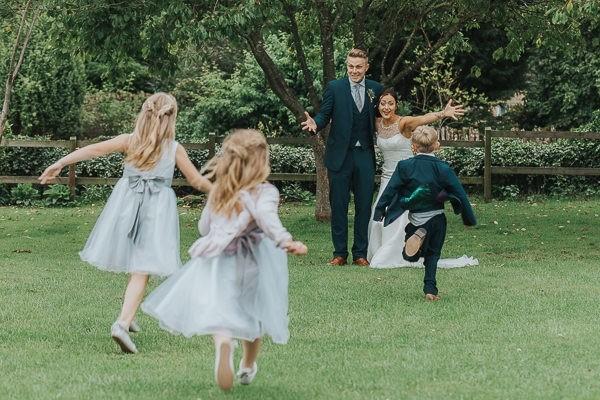 Children running towards bride and groom