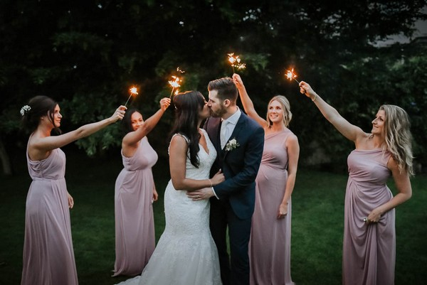 Bridesmaids holding sparklers around bride and groom