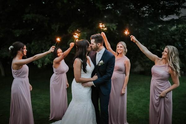 Bridesmaids holding sparklers around bride and groom