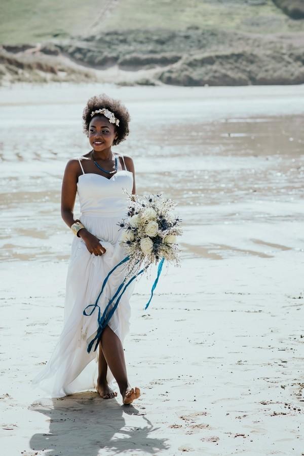 Bride walking on beach carrying bouquet