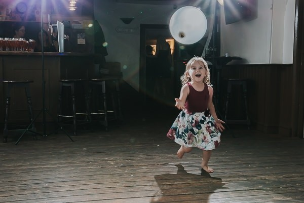 Young girl playing with balloon on dance floor at wedding