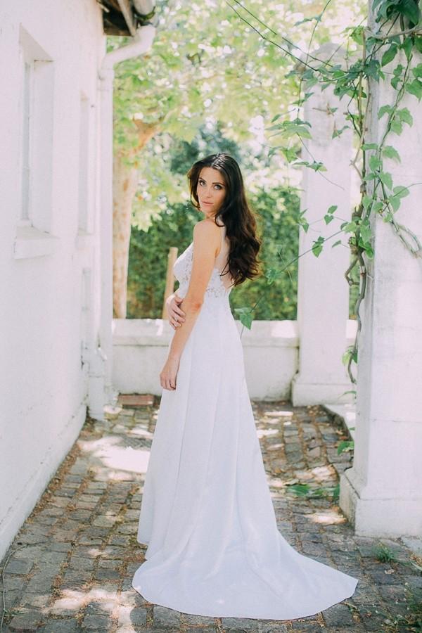 Bride looking over shoulder showing back of wedding dress