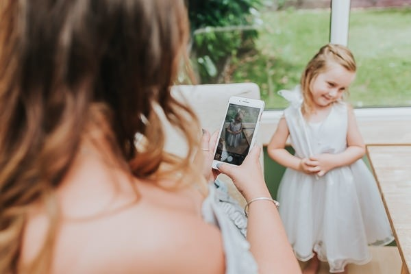 Bridesmaid taking picture of flower girl