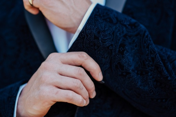 Groom touching suit jacket cuff