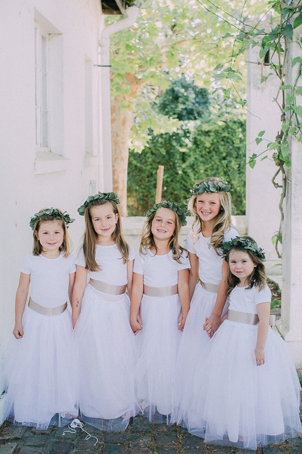 Flower girls in white dresses with floral crowns