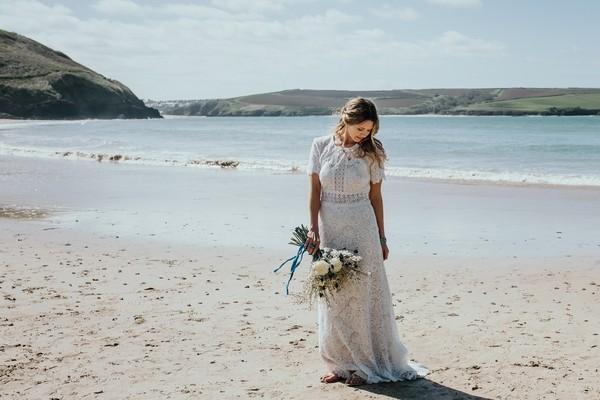 Bride on beach looking down