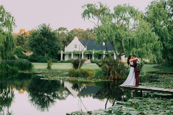 Bride and groom by lake at Natte Valleij wedding