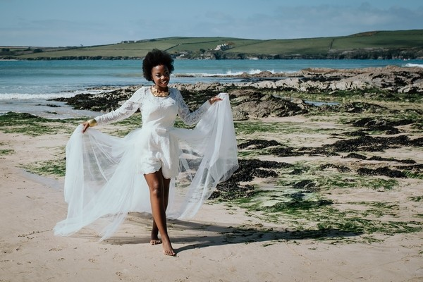 Bride holding out skirt of wedding dress as she walks on the beach
