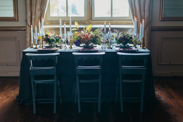 Wedding table with dark tablecloth and chairs