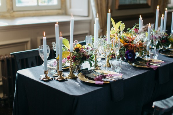 Flowers and candles on wedding table with dark tablecloth