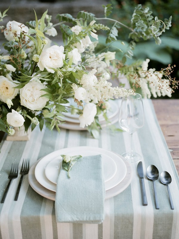 Simple and elegant wedding place setting with flowers and striped runner