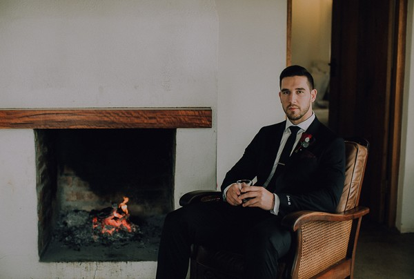Groom sitting in chair by fire
