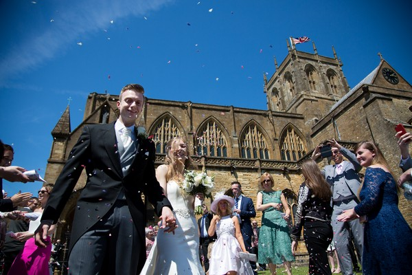 Wedding confetti moment outside Sherborne Abbey