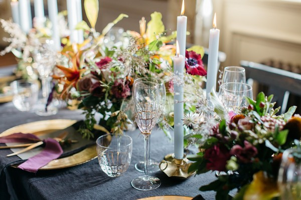 Flowers, candles and glassware on dark tablecloth