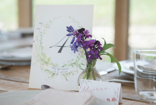 Small vase of purple flowers next to table number